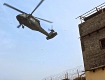 A U.S. Army UH-60 Black Hawk helicopter prepares to land as U.S. soldiers provide security from a building window at the Khyber Border Coordination Center near Torkham Gate at the Afghanistan-Pakistan border in Afghanistan's Nangarhar province, Jan. 4, 2015.