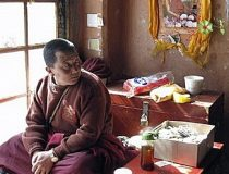 A monk sits beside an altar at Drepung Temple in Lhasa