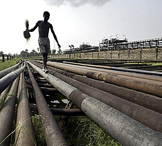 civilian walking along pipes in the Niger Delta