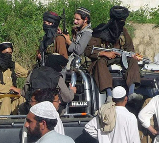 Pakistani Taliban fighters sit in the back of a truck with their weapons in Buner