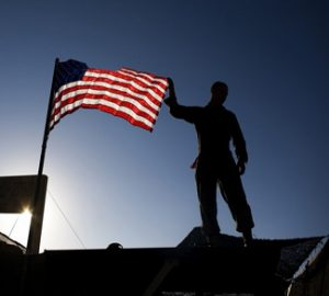 A U.S. Marine from 3rd Battalion 4th Marines, adjusts the U.S. flag on the top of his tent on base Delaram in Nimroz province