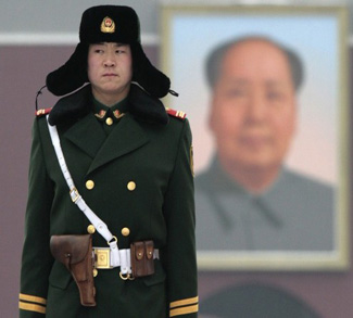 A paramilitary policeman stands guard in front of a portrait of former Communist Party chairman Mao Zedong at Tiananmen Square in Beijing