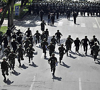 Chinese security forces chase off protesters during a demonstration at the centre of Urumqi