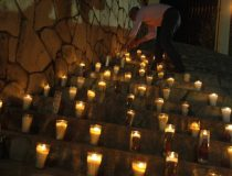 A resident lights a candle on the steps of a church in memory of Edelmiro Cavazos, mayor of the tourist town of Santiago