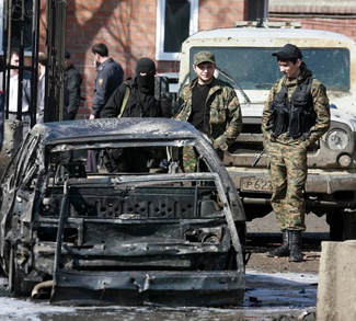 Interior Ministry servicemen stand next to a car that was blown up during a bombing in Karabulak
