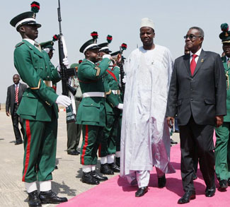 Ghana's President John Atta Mills inspects a guard of honour upon arrival for the ECOWAS meeting in Abuja