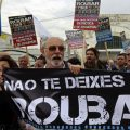 """People protest in front of Finance Ministry holding a banner saying """"Don't be robbed"""" in Lisbon"""