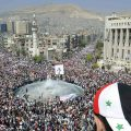 Youth with Syrian flag on hat watches crowd