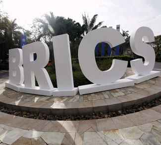 A man walks past a signage decoration for the BRICS summit outside Sheraton Hotel in Sanya