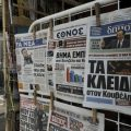 Newspapers are displayed at a kiosk in A