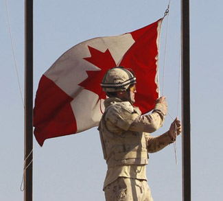Canadian Army Private Drapeau lowers Canadian national flag during ceremony marking Canadian handover of forward fire base Zangabad to U.S. forces, in Panjwai district in Kandahar province