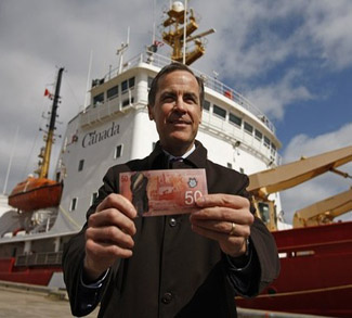 Bank of Canada Governor Mark Carney holds the new Canadian 50 dollar bill, made of polymer, in front of the CCGS Amundsen, the Arctic research vessel depicted on the back of the new bill, in Quebec City