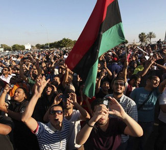 Protesters wave a Kingdom of Libya flag as they demonstrate against the allocation of seats for elections to Libya's National Congress, in Benghazi