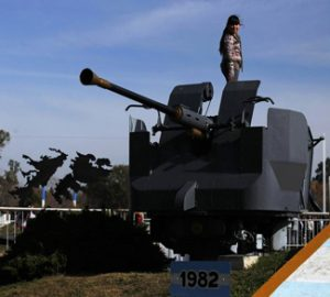 A girl stands on a cannon at an Argentine Falklands