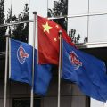 Flags of China National Offshore Oil Corp (CNOOC) fly beside the China flag in front of its headquarters building in Beijing