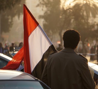A human rights protestor in Egypt carries an Egyptian flag.