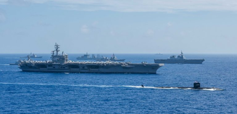 PHILIPPINE SEA (June 14, 2017) Ships from the Indian Navy, Japan Maritime Self-Defense Force (JMSDF) and the U.S. Navy sail in formation during Malabar 2018. Malabar 2018 is the 22nd rendition of the exercise and the first time it has been hosted off the coast of Guam. Malabar is designed to advance military-to-military coordination in a multinational environment between the U.S., Japan and Indian maritime forces. (U.S. Navy photo by Mass Communication Specialist 3rd Class Erwin Jacob V. Miciano/Released) 180615-N-VI515-648, modified