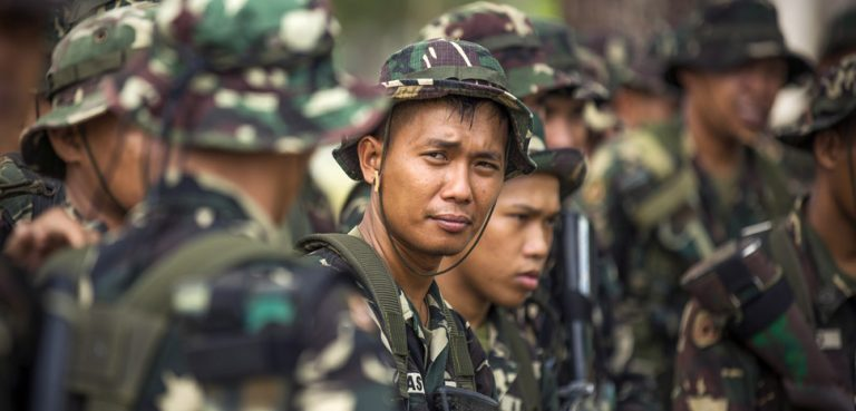 Philippine Army Pfc. Alex Jatass, center, waits to start helicopter insert and extract training with U.S. soldiers on Fort Magsaysay, Philippines, April 29, 2014. U.S. Marine Corps photo by Staff Sgt. Pete Thibodeau , modified, public domain
