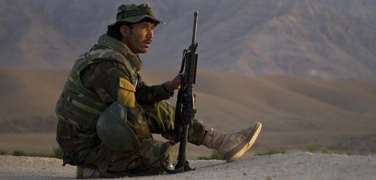 An Afghan commando, with the Afghan National Army's 3rd Commando Kandak, provides security overwatch via rooftop for fellow Commandos and U.S. Navy SEALs , with Special Operations Task Force – South, during a village clearing operation in Khakrez district, May 6, Kandahar province, Afghanistan. Missions such as these are conducted on a regular basis to hinder Taliban influence throughout the province and increase security for the general populace.