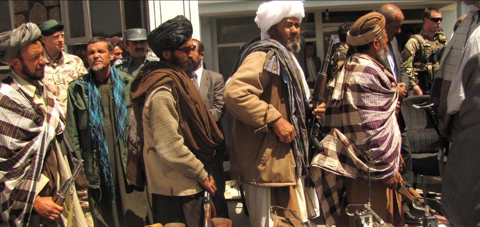 Former Taliban fighters hand in their guns / GHŌR, Afghanistan (May 28, 2012) – Former Taliban fighters line up to handover their Rifles to the Government of the Islamic Republic of Afghanistan during a reintegration ceremony at the provincial governor's compound. The re-integrees formally announced their agreement to join the Afghanistan Peace and Reintegration Program during the ceremony. (Department of Defense photograph by Lt. j. g. Joe Painter/RELEASED) / https://commons.wikimedia.org/wiki/File:Former_Taliban_fighters_return_arms.jpg