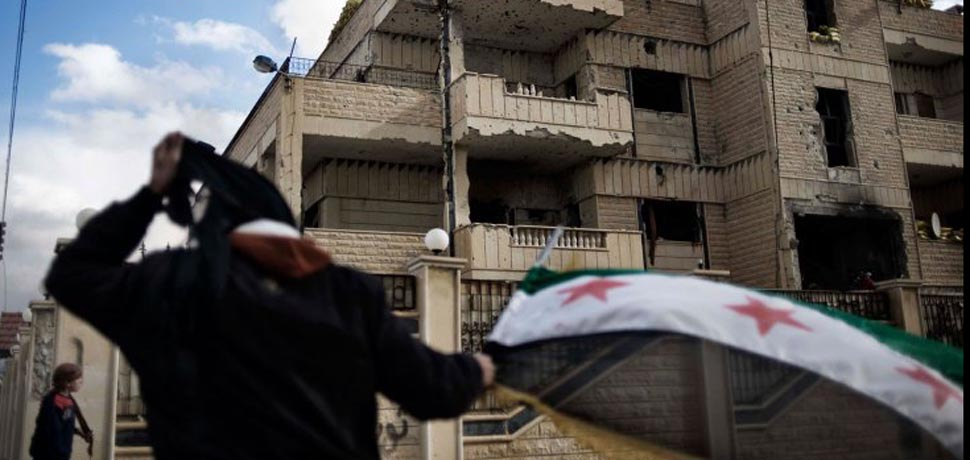 A man waves the old Syrian flag in front of the former police st, cc Flickr Freedom House, modified, https://creativecommons.org/licenses/by/2.0/