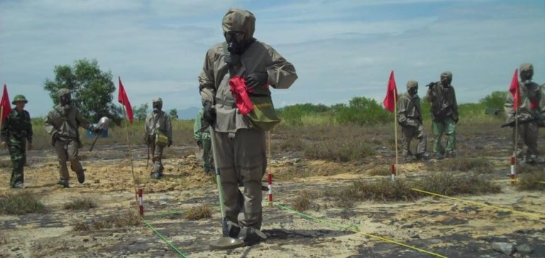 VietnamUXO, CC USAID Vietnam, modified, https://commons.wikimedia.org/wiki/File:Vietnam_starts_UXO_clearance_in_Danang_ahead_of_USAID-supported_dioxin_remediation_partnership_with_Vietnam_(5848584594).jpg