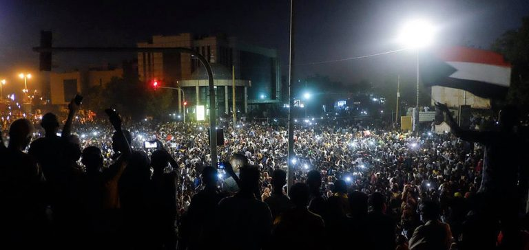 Protest in Khartoum near army HQ, cc M. Saleh, modified, https://commons.wikimedia.org/w/index.php?title=Special:Search&title=Special:Search&redirs=0&search=khartoum+protest&fulltext=Search&fulltext=Advanced+search&ns0=1&ns6=1&ns14=1&advanced=1&searchToken=6nlw8xdx3i85u6thqgb3fvhfr#%2Fmedia%2FFile%3ASudanese_protestors_gathering_infront_of_Army_HQ.jpg