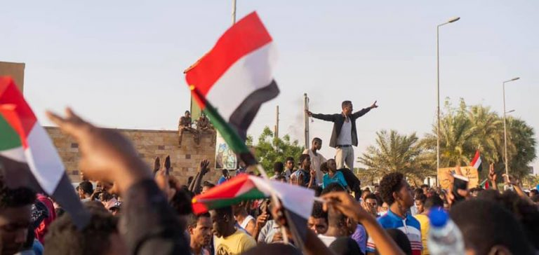 Sudan protests 2019, CC M. Saleh, modified, Wikicommons, https://commons.wikimedia.org/w/index.php?title=Special:Search&title=Special:Search&redirs=0&search=khartoum+protests&fulltext=Search&fulltext=Advanced+search&ns0=1&ns6=1&ns14=1&advanced=1&searchToken=1a26j4o5p9lklfiy2kh8biz98#%2Fmedia%2FFile%3ASudanese_protestors_chanting.jpg