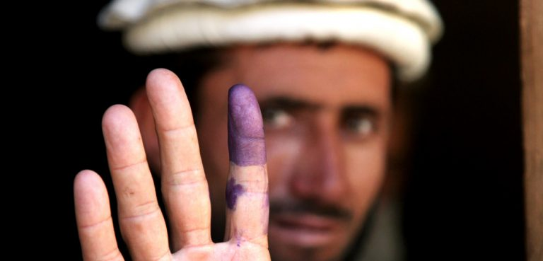 An Afghan elder shows his inked finger to show he voted during the heavily anticipated Afghanistan elections in Barge Matal, Afghanistan, Aug. 20, 2009. Afghanistan village elders are considered to be the role models and leaders among the Afghan civilians. U.S. Army soldiers helped provide security during the elections. U.S. Army photo by Staff Sgt. Christopher Allison, modified, https://commons.wikimedia.org/wiki/File:Inked_finger.jpg