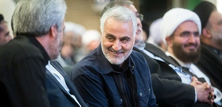 cc Erfan Kouchari, modified, Tansim news agency, https://commons.wikimedia.org/wiki/File:Major_General_Qassem_Soleimani_at_the_International_Day_of_Mosque_(2).jpg