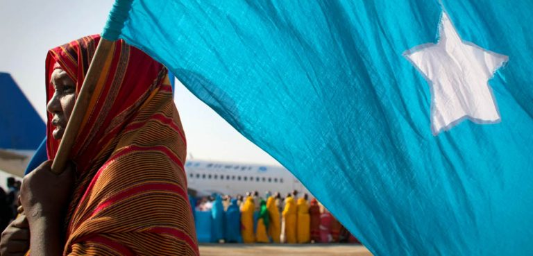SOMALIA, Mogadishu: In a photograph released by the African Union-United Nations Information Support Team 25 March, a woman holds the Somali flag at Mogadishu International Airport during a ceremony held to recieve the casket containing the body of fomer Somali president Abdullahi Yusuf Ahmed who died aged 77 on Friday at a hospital in the Gulf State of Abu Dhabi. AU-UN IST PHOTO / STUART PRICE. / SomaliFlag, cc Flickr, modified, AMISOM Public Information, public domain