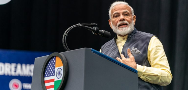 Prime Minister Modi in Texas, USA. CC Flickr White House, public domain, modified, Prime Minister Narendra Modi of India addresses his remarks on stage Sunday, Sept. 22, 2019, at a rally in honor of Prime Minister Modi at NRG Stadium in Houston, Texas. (Official White House Photo by Shealah Craighead)