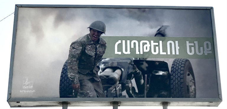 Billboards in Yerevan have been displaying footage released by the Armenian Ministry of Defence since the beginning of the conflict.cc Wikicommons Գարիկ Ավագյան, modified, https://en.wikipedia.org/wiki/2020_Nagorno-Karabakh_war#/media/File:Photo_of_the_Armenian_soldier_from_the_frontline_(Yerevan,_Armenia).jpg