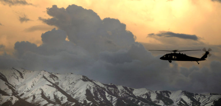 A UH-60 Black Hawk helicopter flies near Bagram Airfield, Afghanistan, March 22, 2007. (U.S. Air Force photo by Tech. Sgt. Cecilio M. Ricardo Jr, cc Flickr US Army, modified, https://www.flickr.com/photos/soldiersmediacenter/447153754/in/photolist-FvMeu-9i9qf3-9i9pmN-5wDz7N-9Xonsg-3ctN1a-2Nx4ov-9i9mG3-KBRT9-dNM8Yg-2Nx4Ca-dQPGQS-eSe9Ge-KBWMq-9XrokA-8RsGEh-dNyGHU-dP79V3-dP78X9-7z9kxr-7z9kDr-9XrgtL-9i9ygd-dP1yJk-9i6oK6-5wAskW-NnY2u-9i6x32-KBWMs-dQJ6Z4-KBWMu-9XoqvM-5ienyD-9i9DzU-9i6pUn-9i6ny2-KBRT5-NnWRC-9i9xME-61GStp-7z9kpV-9i6nce-9i6yfa-7zd7Eq-9i9st5-N5zy5-N5zxW-KBXbL-KBXbJ-7RiooV.)