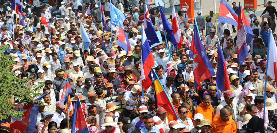 Opposition supporters wave national flags of some Western countries who were signatory parties to the 22 year old Paris Peace Agreement, Phnom Penh, Oct 24, 2013. (Heng Reaksmey/VOA Khmer), cc Heng Reaksmey, modified, https://commons.wikimedia.org/w/index.php?title=Special:Search&redirs=0&search=cambodia%20CNRP&fulltext=Search&ns0=1&ns6=1&ns14=1&title=Special:Search&advanced=1&fulltext=Advanced%20search#/media/File:CNRP_protesters_raise_flags.jpg
