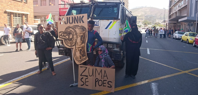 an anti-Zuma protest from 2017, cc Discott, modified, https://commons.wikimedia.org/w/index.php?title=Special:Search&title=Special:Search&redirs=0&search=president+zuma&fulltext=Search&fulltext=Advanced+search&ns0=1&ns6=1&ns14=1&advanced=1#/media/File:Anti-Zuma_protest_Cape_Town.jpg
