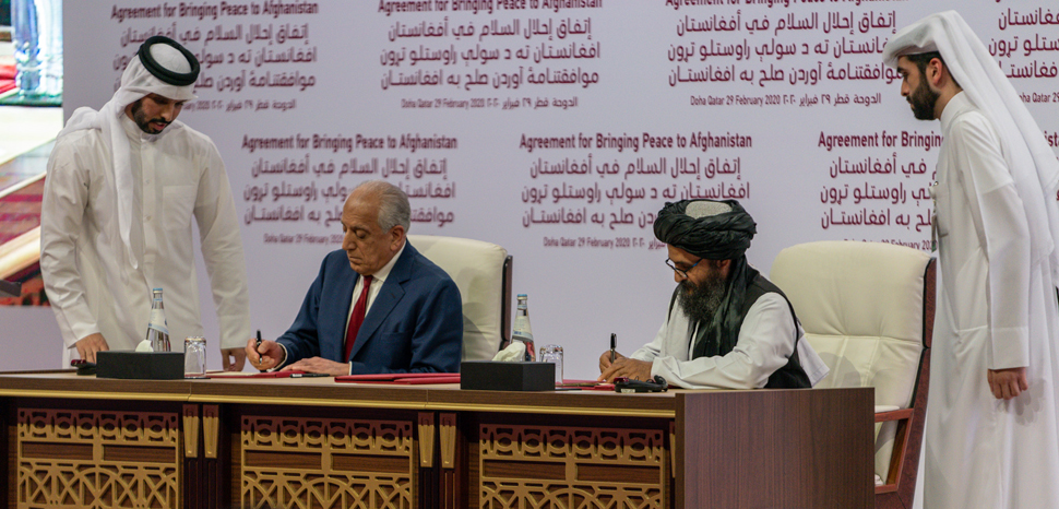 US representative Zalmay Khalilzad (left) and Taliban representative Abdul Ghani Baradar (right) sign the agreement in Doha, Qatar on February 29, 2020. [State Department photo by Ron Przysucha/ Public Domain], cc US State Department, modified,