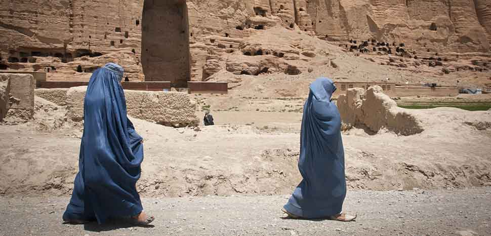 Two women walk past the huge cavity where one of the ancient Buddhas of Bamiyan, known to locals as the