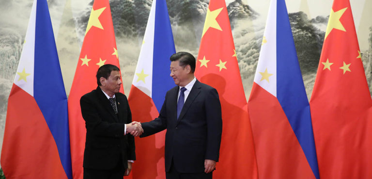 President Rodrigo Roa Duterte and People's Republic of China President Xi Jinping shake hands prior to their bilateral meetings at the Great Hall of the People in Beijing on October 20. Photo by King Rodriguez/PPD, cc Philippine government, modified, https://commons.wikimedia.org/wiki/File:President_Duterte_handshake_with_President_Xi.jpg