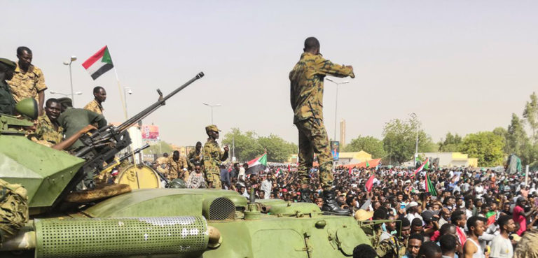 English: Sudanese soldeirs stand guard around armoured military vehicles as demonstrators continue their protest against the regime near the army headquarters in the Sudanese capital Khartoum, cc Agence France-Presse, modified, https://commons.wikimedia.org/wiki/File:Sudan_coup_military_afp.jpg