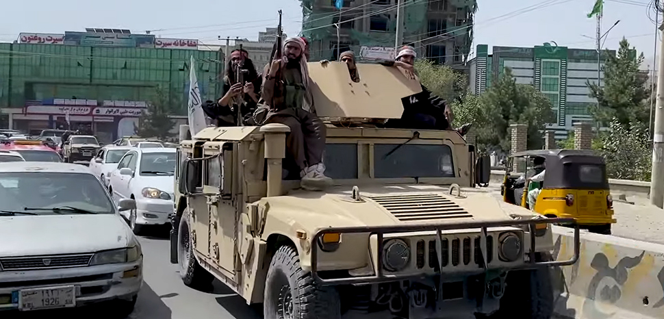 Taliban fighters in a US-supplied Humvee; modified, cc VOA, https://en.wikipedia.org/wiki/Fall_of_Kabul_(2021)#/media/File:Taliban_Humvee_in_Kabul,_August_2021_(cropped).png